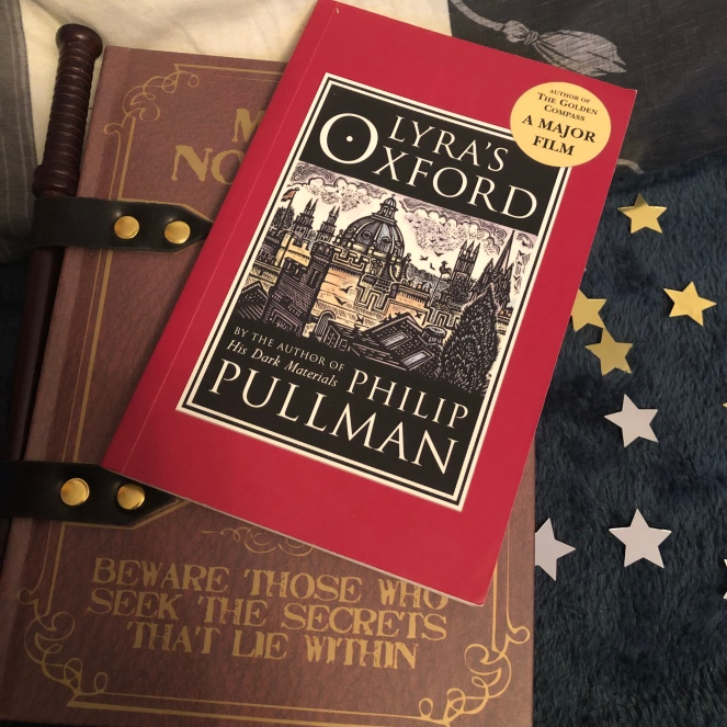 A copy of the book 'Lyra's Oxford' on top of a magical notebook and surrounded by stars