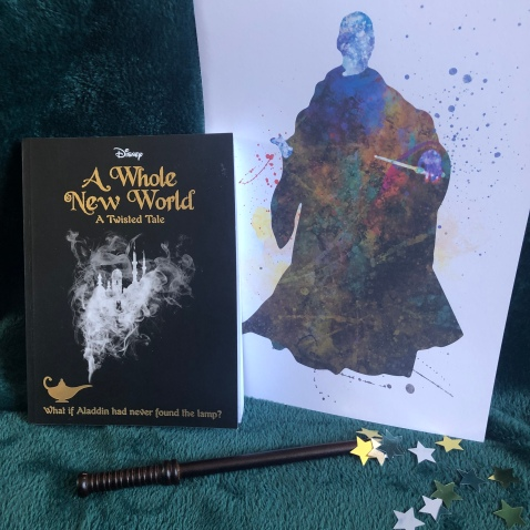 The book A Whole New World standing next to an art print of Lord Voldemort. A wand and some stars lay nearby.