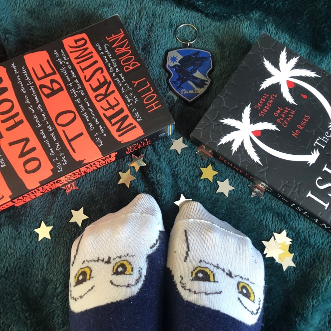 Two books (The Manifesto On How To Be Interesting, & The Island), a Ravenclaw crest keyring, two feet in owl socks, and some sprinkled stars