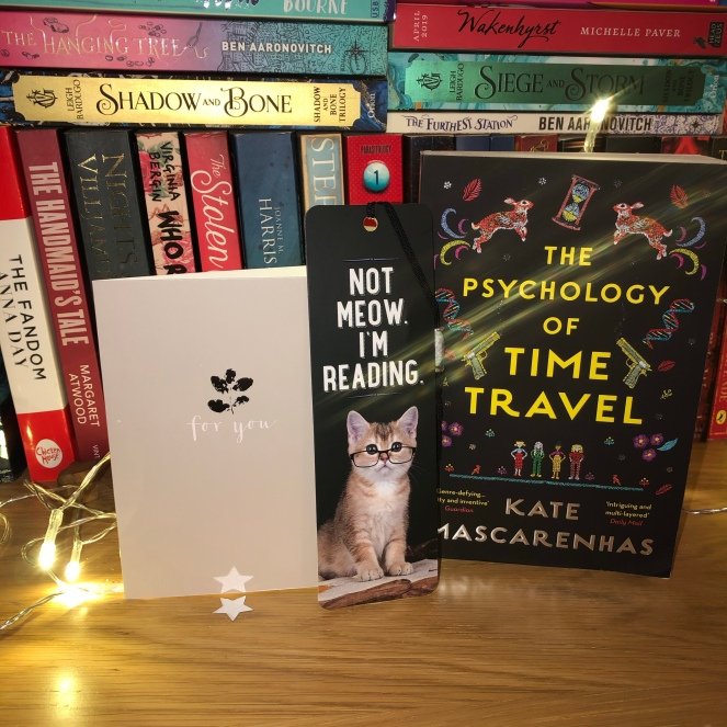 The book 'The Psychology Of Time Travel' by Kate Mascarenhas stands on a bookshelf alondside a cute kitten bookmark and a 'For You' note card. There are fairlylights and other books in the background.