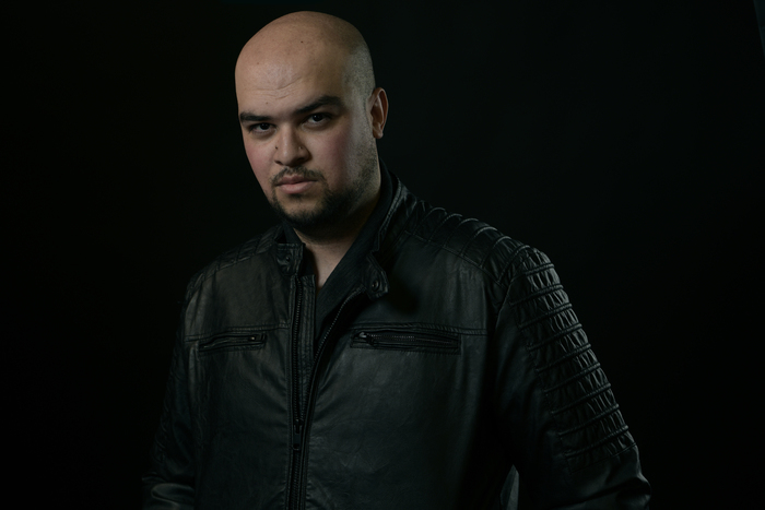 Photograph of Kevin Van Whye, a young, mixed-race man with a bald head and neatly trimmed beard. He is wearing a black jacket and stands before a black background.