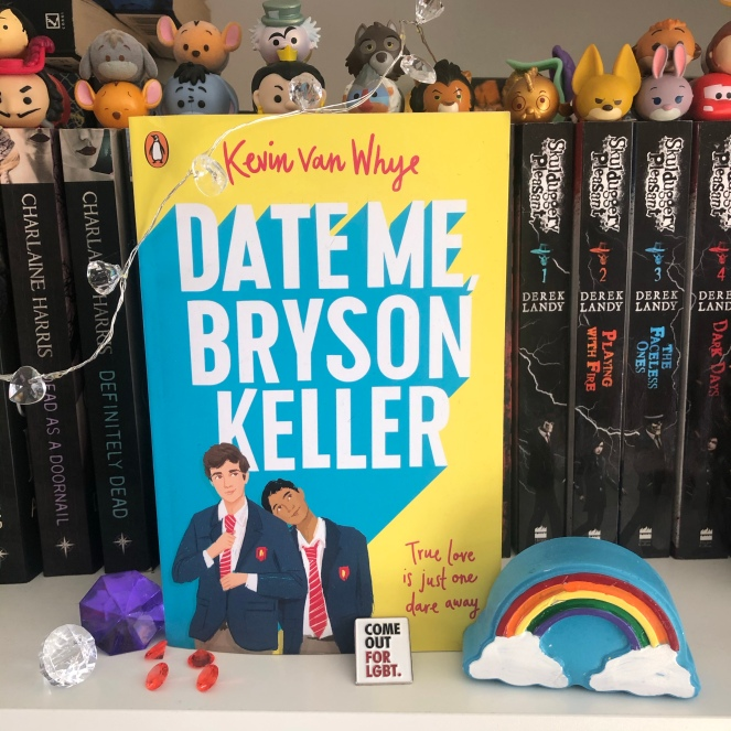 Photograph of the book Date Me, Bryson Keller by Kevin van Whye on a bookshelf. The cover is bright yellow with white and blue lettering and features two boys in school uniforms side by side. One boy is tall and pale skinned and is straightening his tie, the other is brown skinned and resting his head on the other boy's shoulder. A rainbow stands on the bookshelf beside the book, along with some shiny pebbles and a Come Out For LGBT pin-badge.