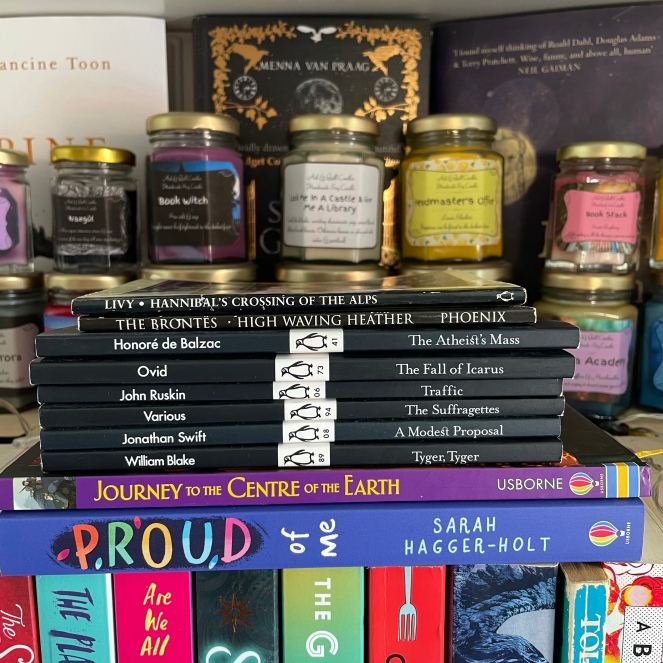 Image of a stack of books on a bookshelf with book-themed scented candles in the background.  The stack contains the following titles: Hannibal's Crossing Of The Alps - Livy High Waving Heather - The Brontes The Atheist's Mass - Honore de Balzac The Fall Of Icarus - Ovid Traffic - John Ruskin The Suffragettes - Various Authors A Modest Proposal - Jonathan Swift Tyger, Tyger - William Blake Journey To The Centre Of The Earth Proud Of Me - Sarah Hagger-Holt